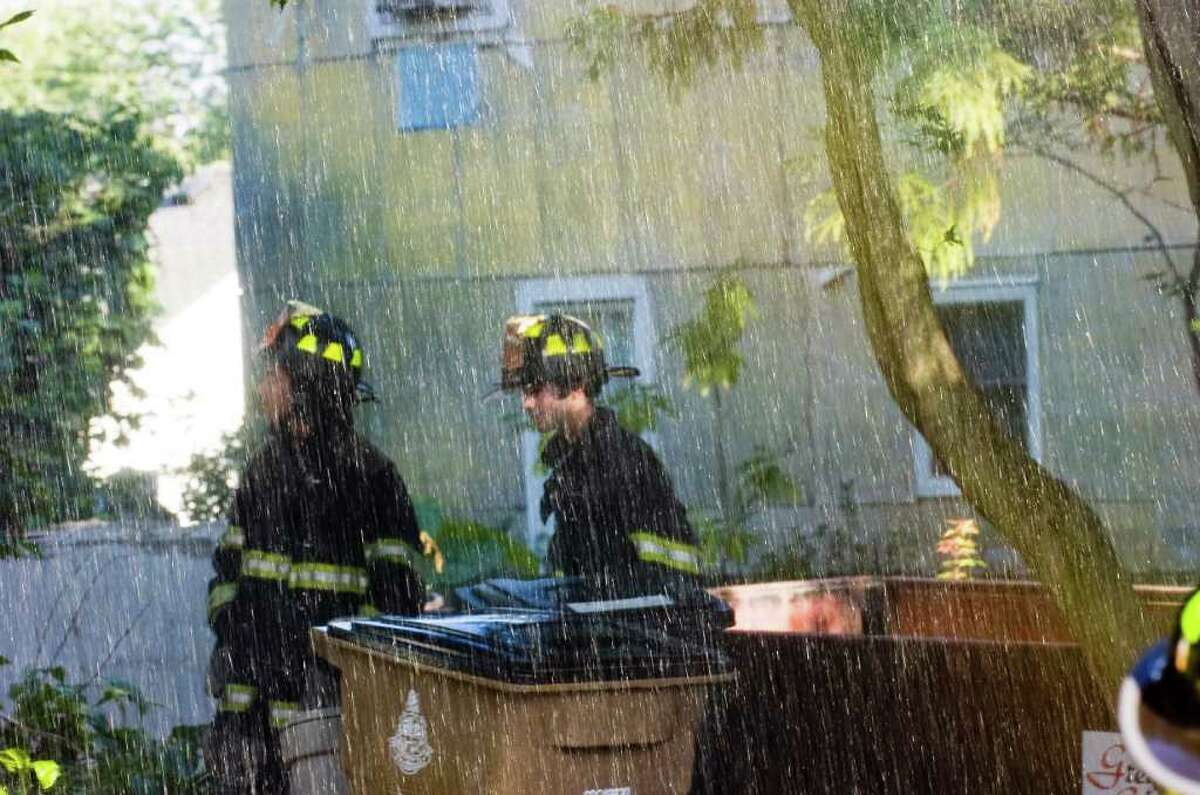 Firefighters stand in a mist as the Belltown Fire Department responds to a house fire at 69 Pepper Ridge Road on Monday, August 30, 2010. The fire began on the first floor of the building which was already gutted due to construction. The exact cause of the fire is still under investigation. Turn of the River and Stamford Fire and Rescue also responded.