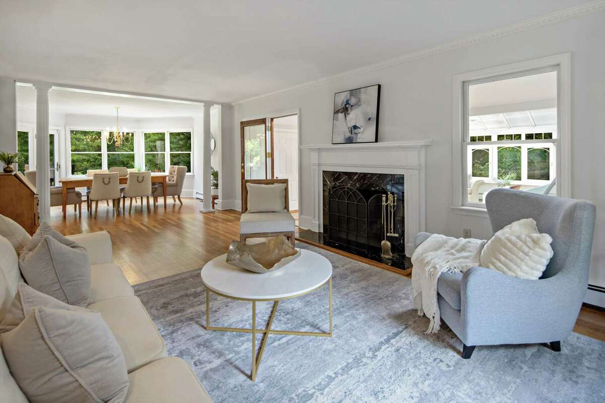 The formal living room has a marble fireplace and two columns separating it from the formal dining room. The Belgium block-lined driveway opens to provide ample parking for family members and guests. A covered walkway with a slate path along the attached two-car garage leads to the casual