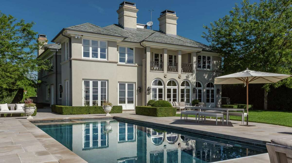The taupe-colored stucco European chateau at 62 Bermuda Road has direct waterfront on Long Island Sound and a Gunite in-ground swimming pool in the yard.