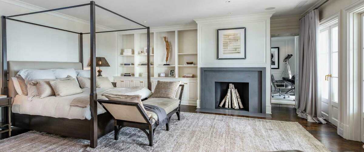 The luxurious master bedroom suite features a fireplace, a wall of built-in shelving and cabinetry, a sitting room or office, private bath, and balcony.