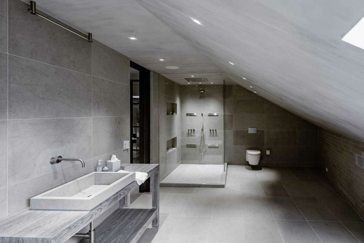 A sizable spa-like bath features a trough sink and large glass shower.