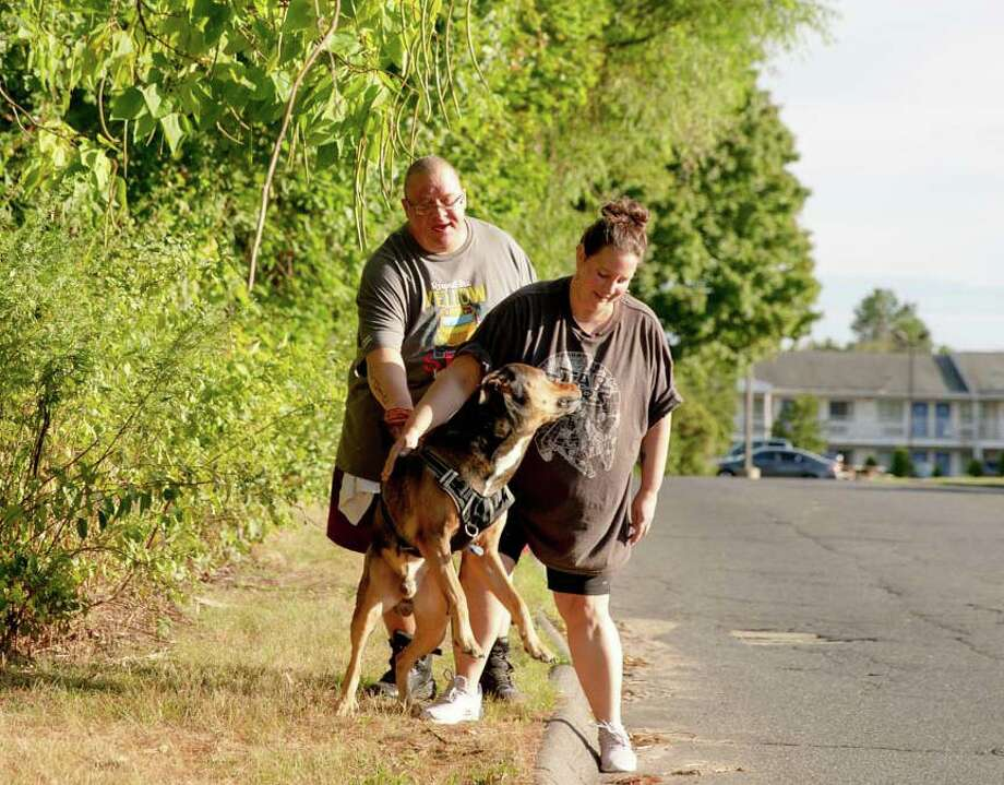 Justin Bidwell, left, and Misty Bidwell calm down their dog Draven on Monday, Aug. 31 in Southington. They have been living in a motel since May 2019 and pay more than $300 a week. Although both are employed as a school bus driver, it's been difficult to save security deposits and recover from low credit scores to live in a stable house. Photo: Yehyun Kim / CTMirror.org / Yehyun Kim