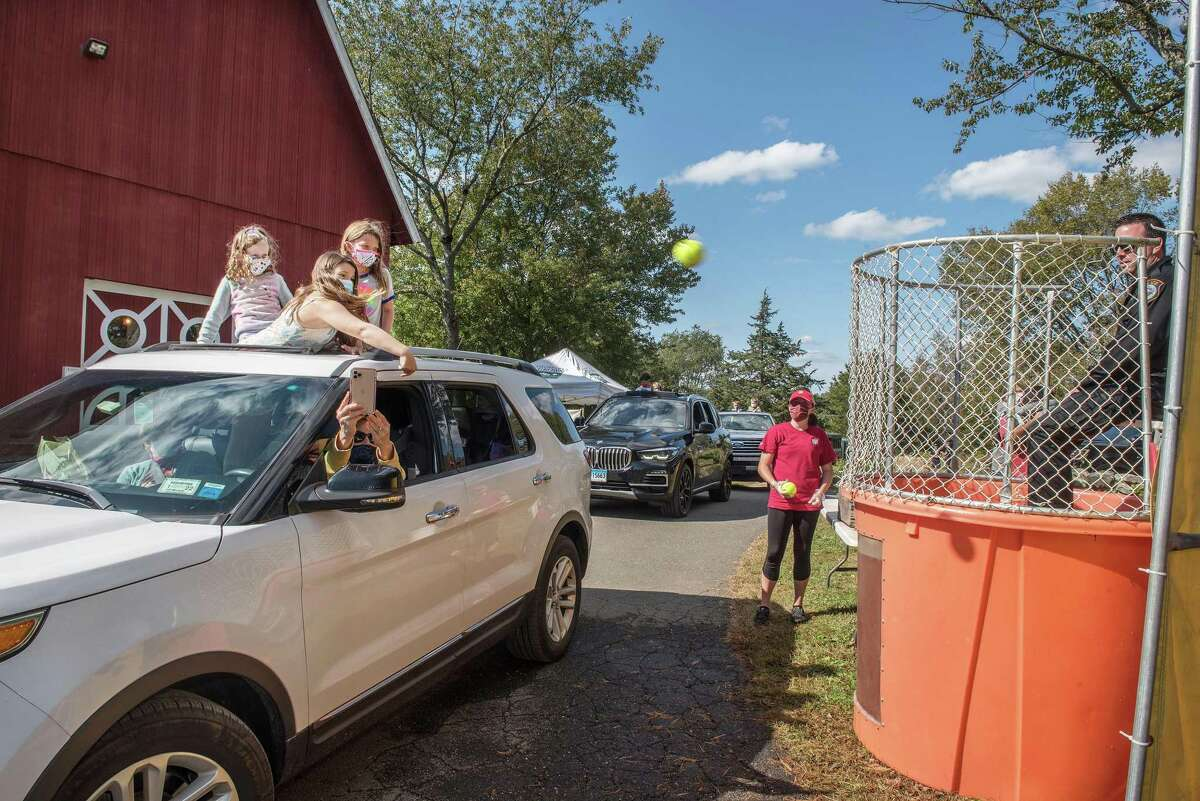 Samara White throws a ball toward the dunk tank as Sonja and Ella Kirschner look on at Ambler Farm Day on Sunday, Oct. 4, 2020, in Wilton, Connecticut.
