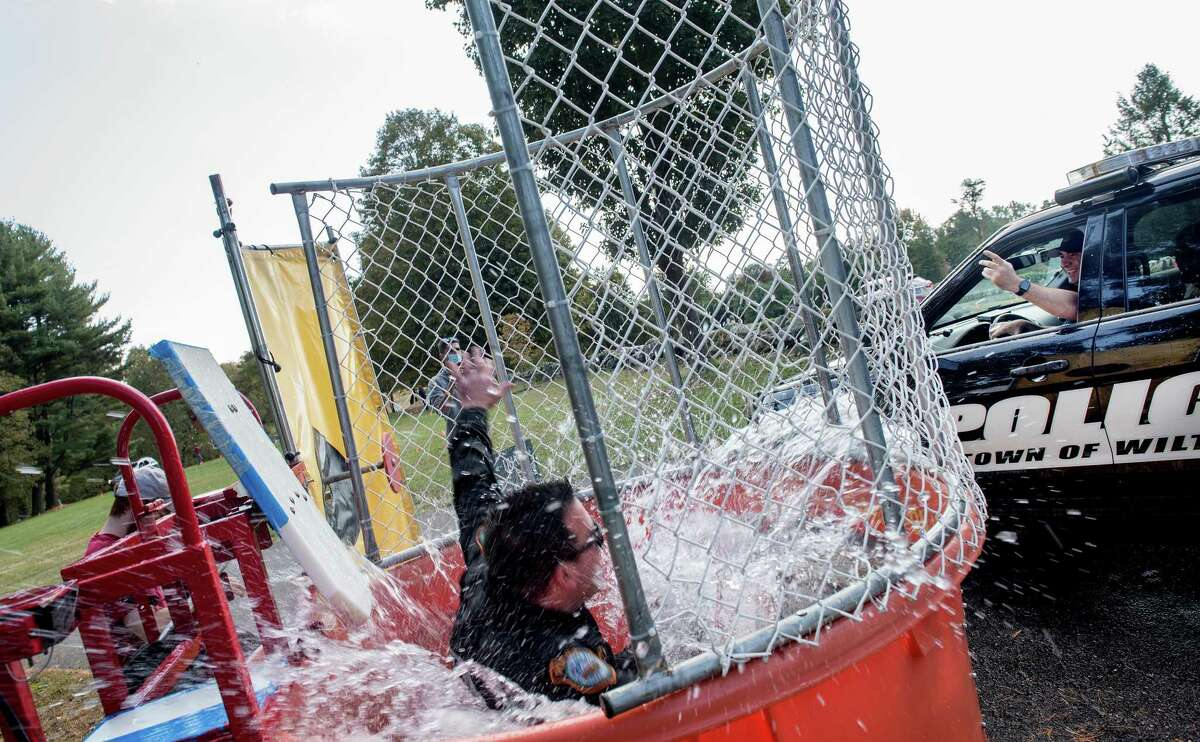 Wilton K9 Officer Patenaude gets dunked at Ambler Farm Day on Sunday, Oct. 4.