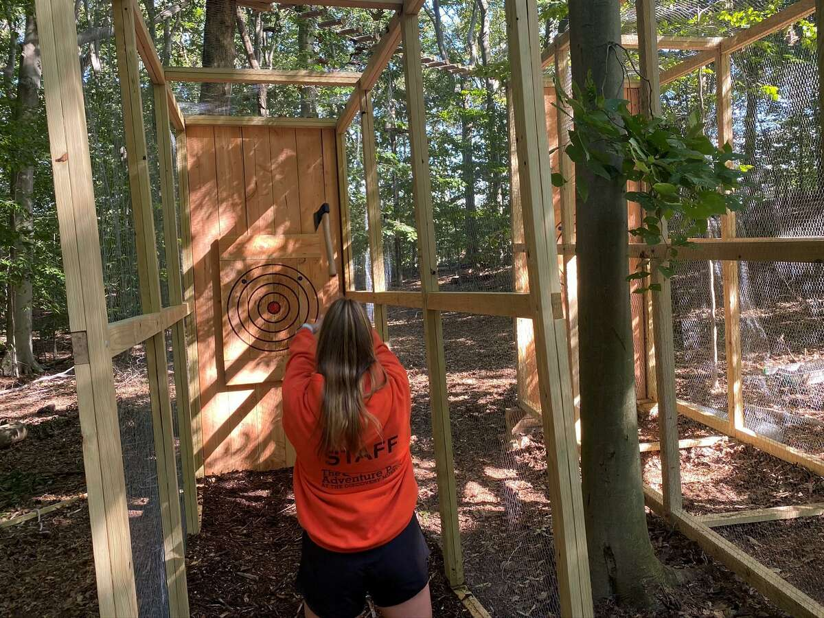 A staffer releases an axe at one of the throwing lanes in Adventure Park Bridgeport.