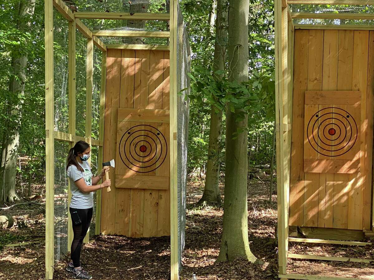 Woman, axe and throwing lane at the outdoor Adventure Park attraction.