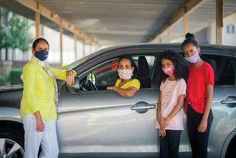 Tsega Mhreteab (center) with her two daughters, Feruz,10, and Delina, 12, next to the donated car the family received from Interfaith Ministries through the help of volunteer Tehmina Masud (left), Wednesday, Oct. 7, 2020, in Houston. The family arrived in Houston as refugees earlier this year, and Interfaith Ministries has realized what a hurdle transportation can be for refugees in Houston.