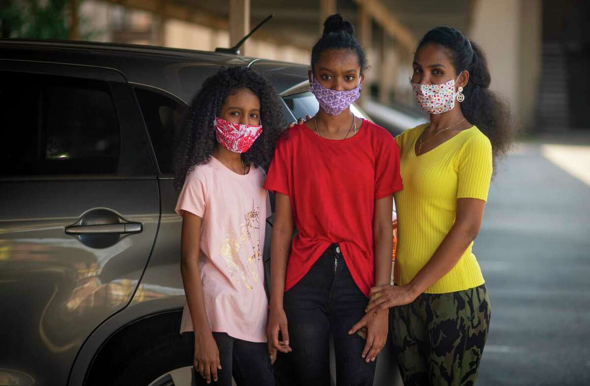Tsega Mhreteab (right) with her two daughters, Feruz (left) and Delina (center) next to the donated car the family received from Interfaith Ministries, Wednesday, Oct. 7, 2020, in Houston. The family arrived in Houston as refugees earlier this year.