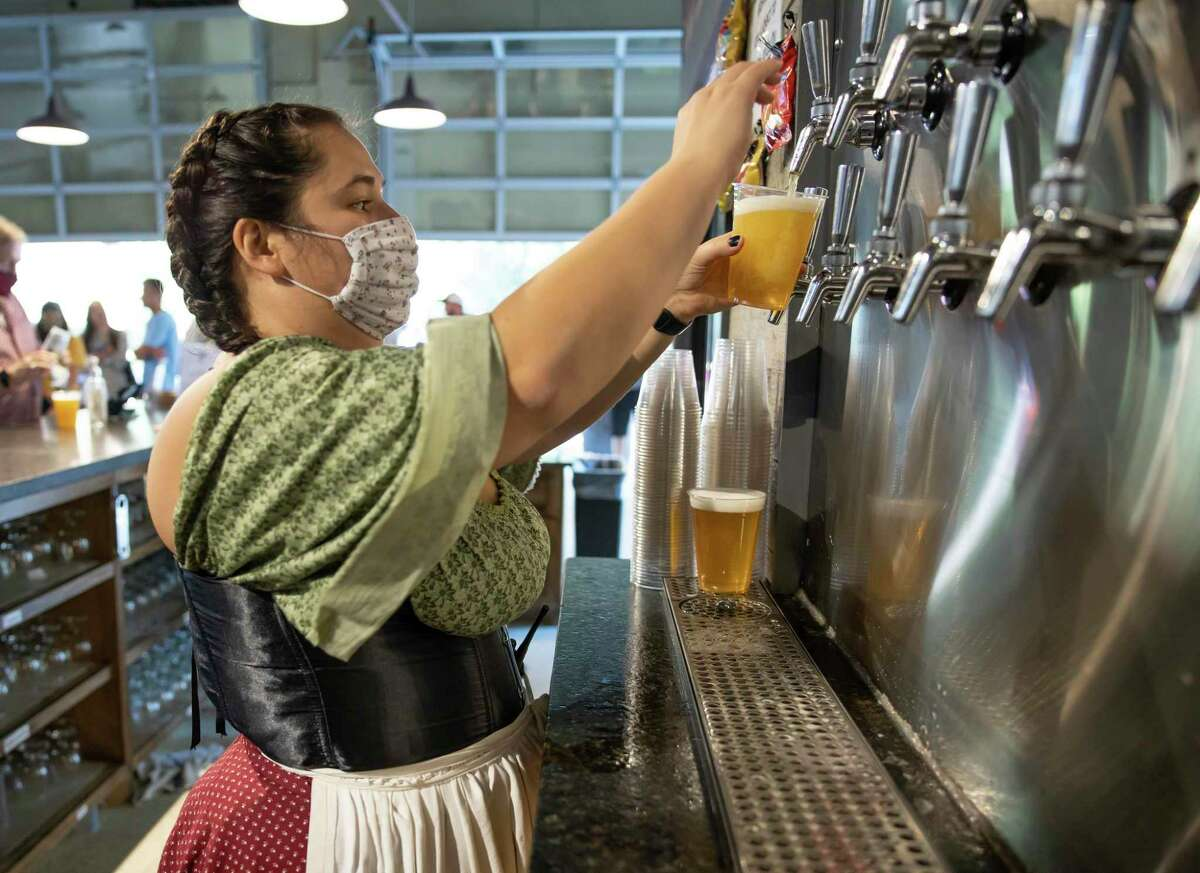 Rissa Kalince fills a cup from tap during Oktoberfest at B-52 in Conroe, Oct. 3, 2020. The brewery made significant changes to this year's celebration of Oktoberfest in response to the pandemic.
