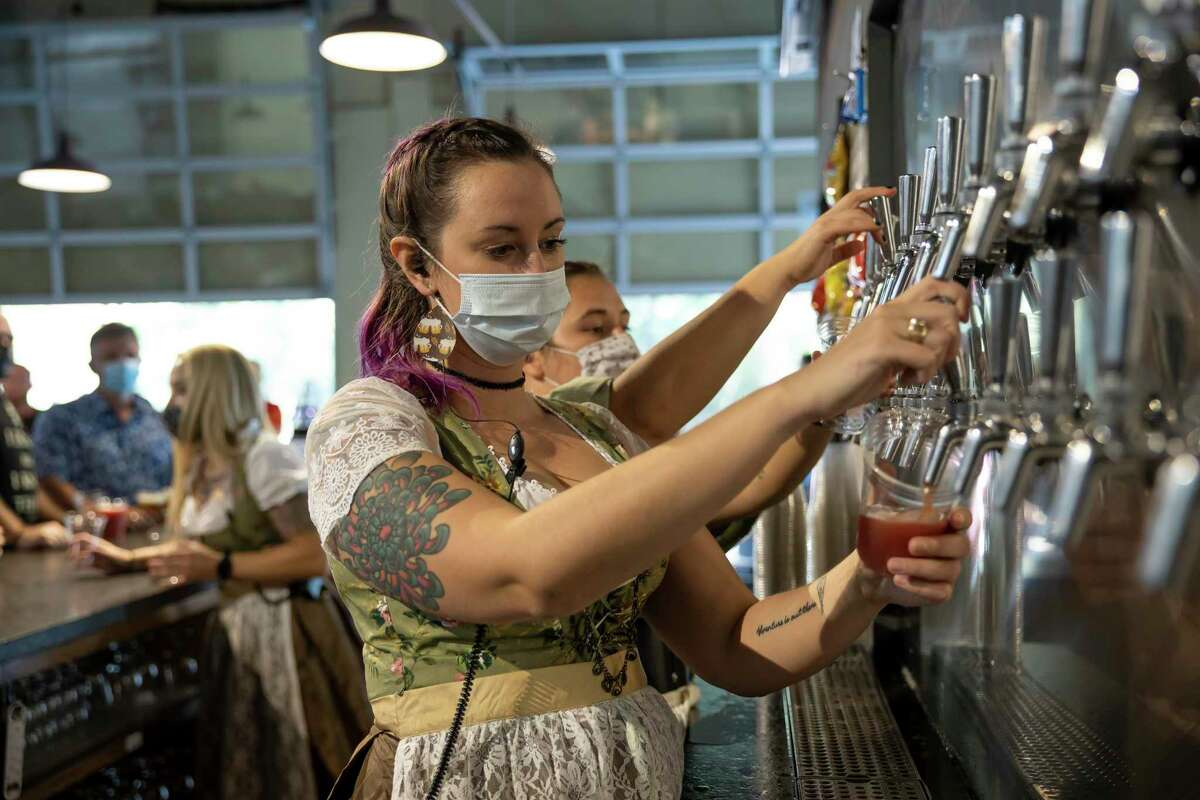 Michelle Lauth fills a cup from tap during Oktoberfest at B-52 in Conroe, Oct. 3, 2020. The brewery made significant changes to this year's celebration of Oktoberfest in response to the pandemic.