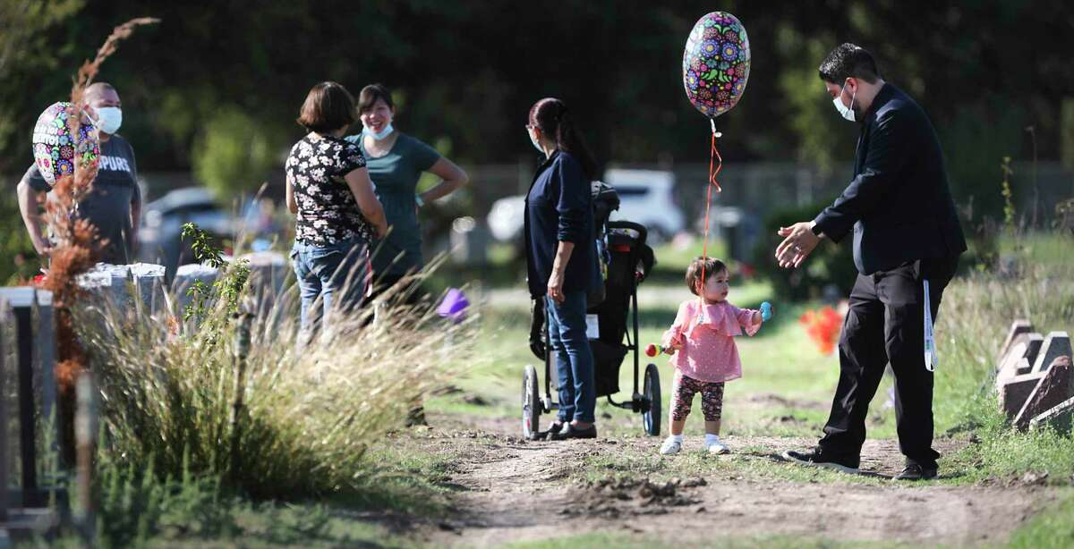 Galo Gutierrez, right, plays with his 1 year-old daughter Annabelle as they and other family members visit the graves of six relatives who died of COVID-19. They were cousins of San Antonio Councilwoman Adriana Rocha Garcia.