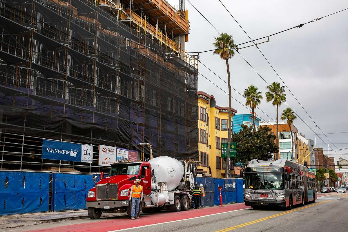 The 14-Mission bus drives past the construction site at 950 Mission St.