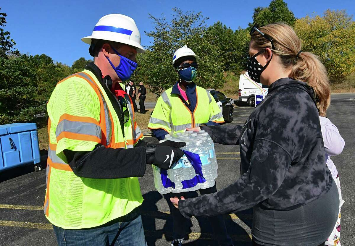 An employee from National Grid hands a case of water to Kristen Padilla of Delmar at the Crossgates Mall parking lot on Friday, Oct. 9, 2020 in Guilderland, N.Y. They also were given a bag of wet ice. Hundreds of people impacted by power outages from Wednesday's storm waited in line for dry ice that never showed up. A limited number of bagged wet ice was given away. (Lori Van Buren/Times Union)