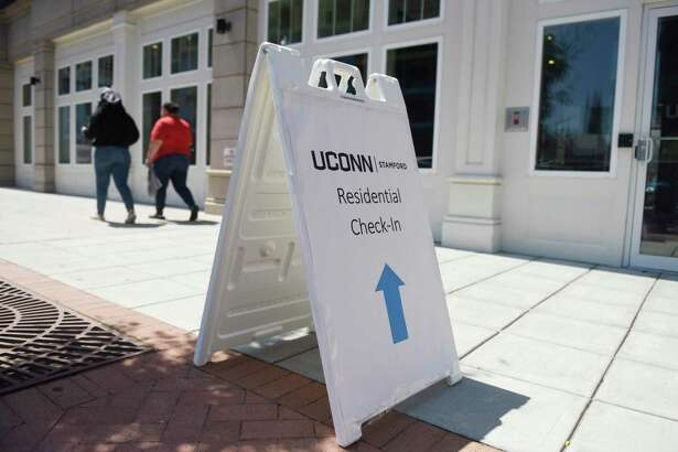 A sign leads to check-in for the student dorms at the UConn Stamford branch in Stamford, Conn. Monday, Aug. 17, 2020. Health experts say active screening for COVID-19 is critical in preventing college outbreaks.