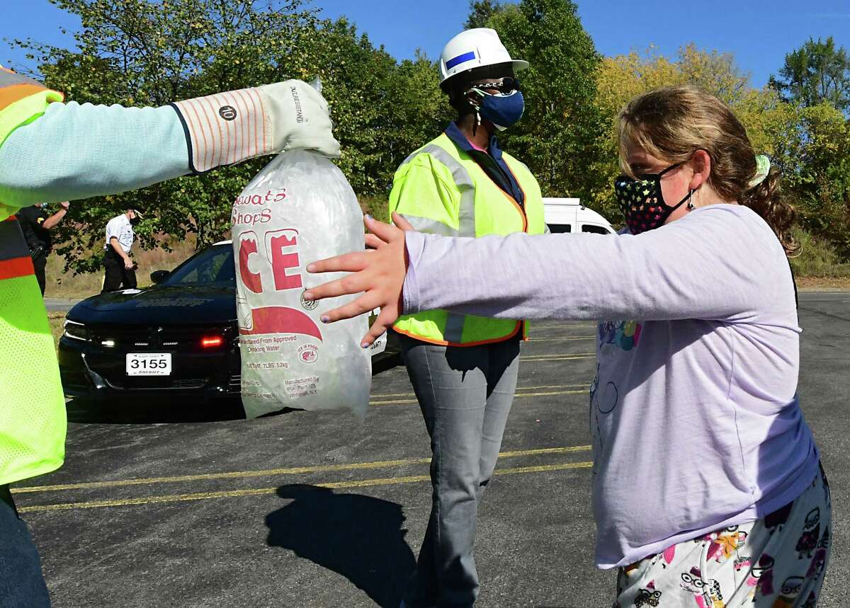 An employee from National Grid hands a bag of wet ice to Maggie Padilla, 9, of Delmar at the Crossgates Mall parking lot on Friday, Oct. 9, 2020 in Guilderland, N.Y. Hundreds of people impacted by power outages from Wednesday's storm waited in line for dry ice that never showed up. A limited number of bagged wet ice was given away. (Lori Van Buren/Times Union)