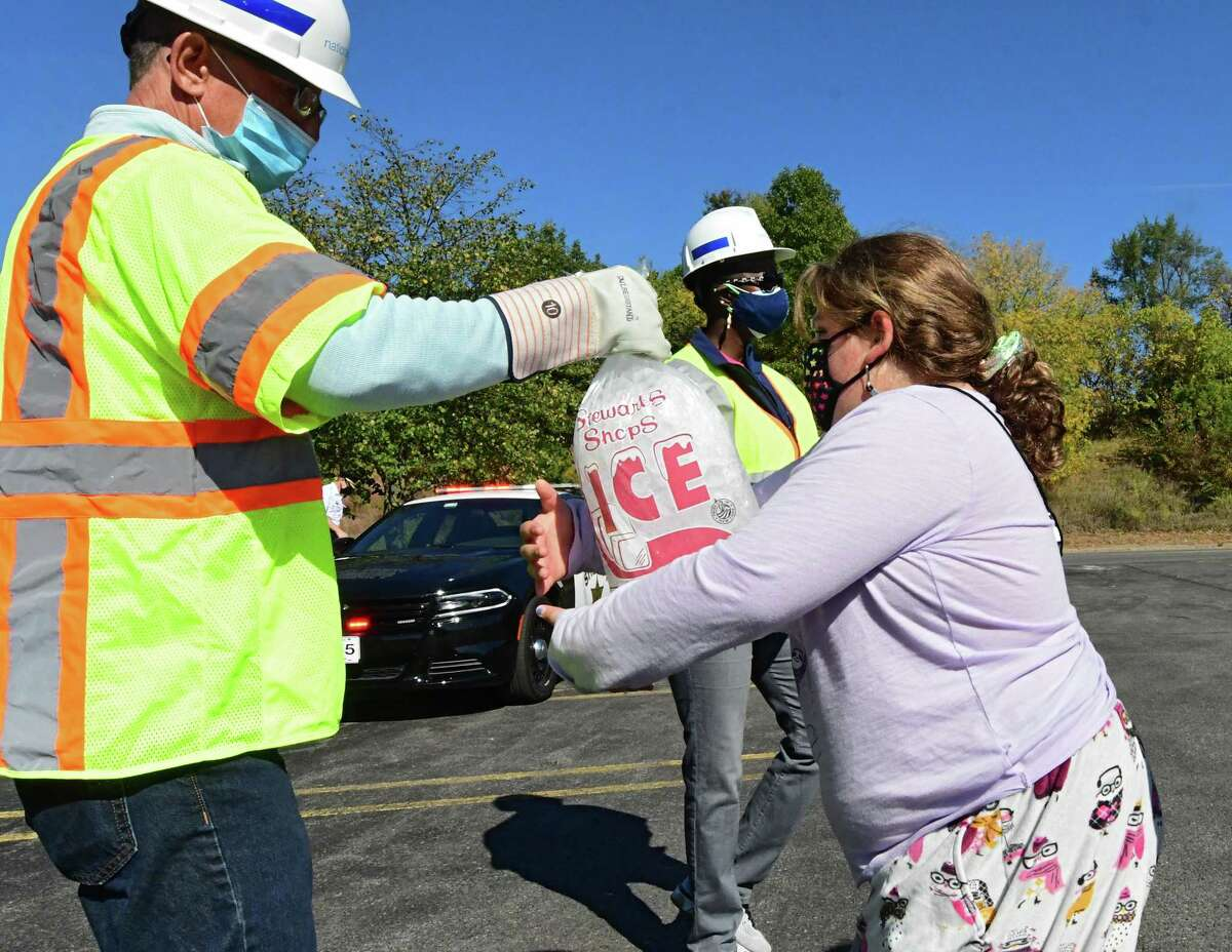 Dan Merrill of National Grid hands a bag of wet ice to Maggie Padilla, 9, of Delmar at the Crossgates Mall parking lot on Friday, Oct. 9, 2020 in Guilderland, N.Y. Hundreds of people impacted by power outages from Wednesday's storm waited in line for dry ice that never showed up. A limited number of bagged wet ice was given away. (Lori Van Buren/Times Union)