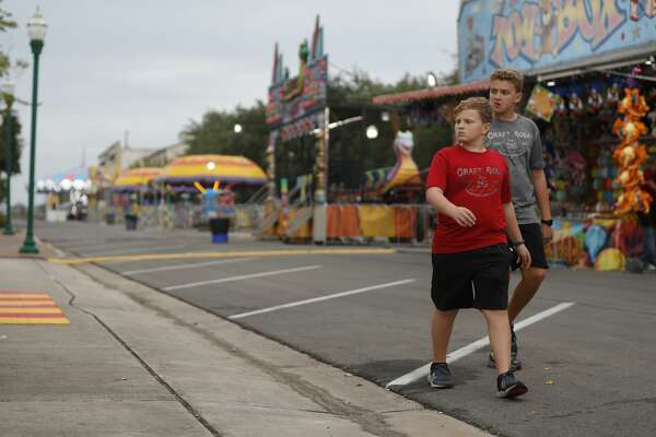Jake Hurst, right, looks over games with his brother, Grant, as light rain falls during the Conroe Cajun Catfish Festival, Thursday, Oct. 8, 2020, in Conroe. The annual festival officially opens Friday with live music, food, rides and more and runs through Sunday.