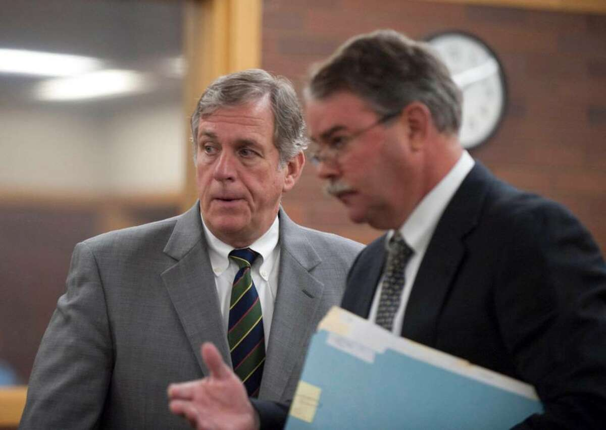 Bethel Conn. First Selectman Robert Burke left, leaves the courtroom with his attorney Thomas Beecher, from his arraignment in Danbury Conn. Superior Court on allegations of harassment charges in connection with repeated phone calls to a woman. (AP Photo/Douglas Healey).