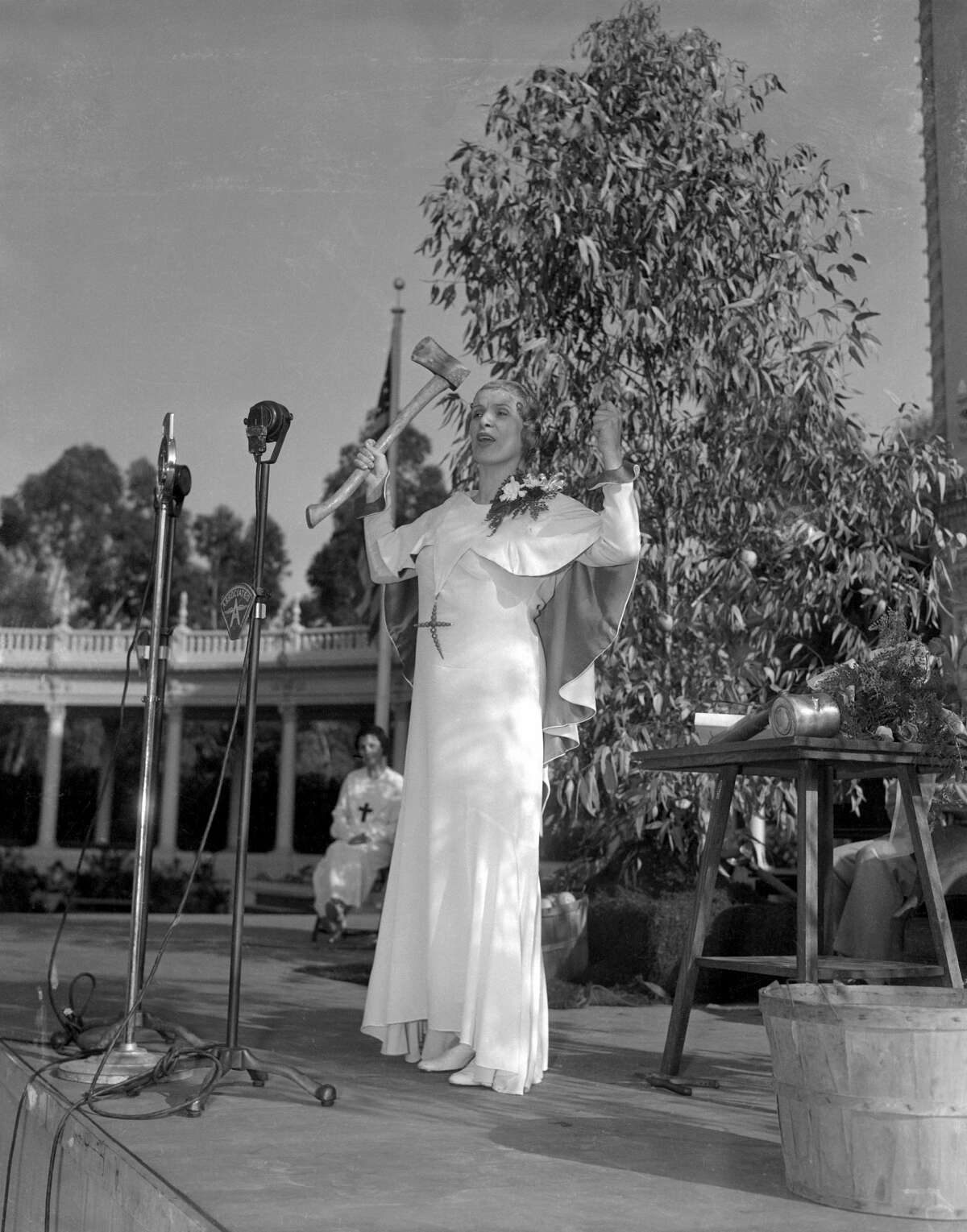 Aimee Semple McPherson, famous evangelist of the Angelus Temple, Los Angeles, wields an axe to illustrate a point in the sermon which she delivered before thousands of followers in the Organ Amphitheater at the California Pacific International Exposition in San Diego.