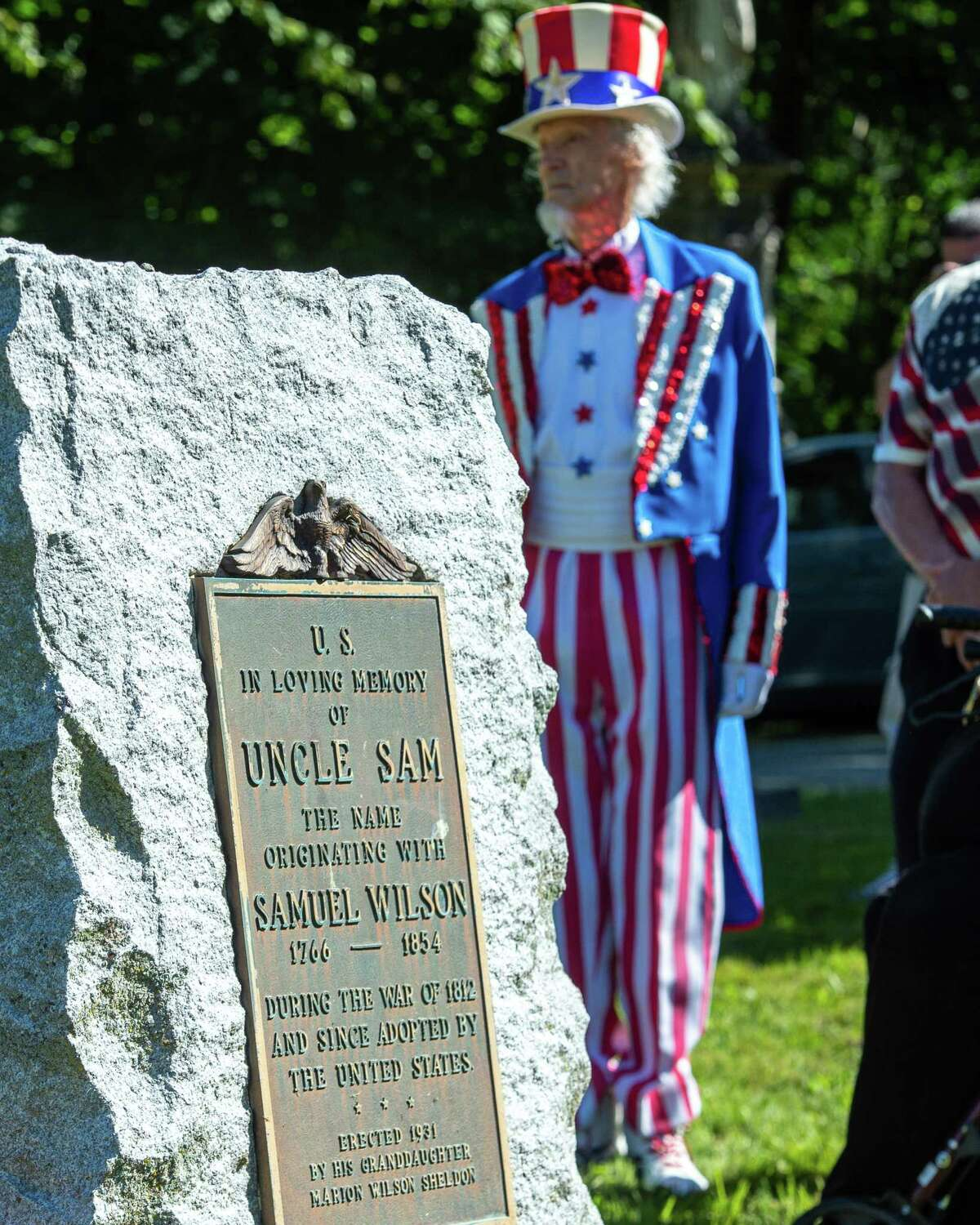 Fred Polnisch is his role as Uncle Sam checks an Uncle Sam historic marker at Oakwood Cemetery in Troy. (Jim Franco / Special to Times Union)