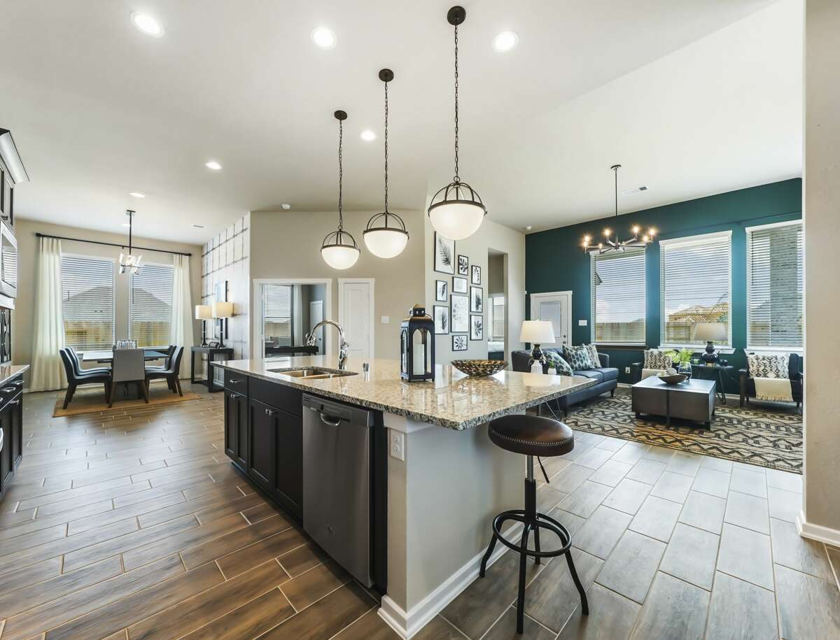 An extended foyer leads to open casual dining, a family room, and an island kitchen with additional countertop dining.