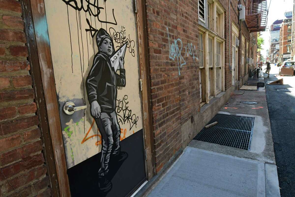 """Artist Joe Iurato, at right, painted this mural titled """"Airplanes"""" in Franklin Alley on Friday, Oct. 9, 2020 in Troy, N.Y. It's based on a boy he met from the Troy Boys and Girls Club. The city's Franklin Alley project is getting closer to a finish. (Lori Van Buren/Times Union)"""