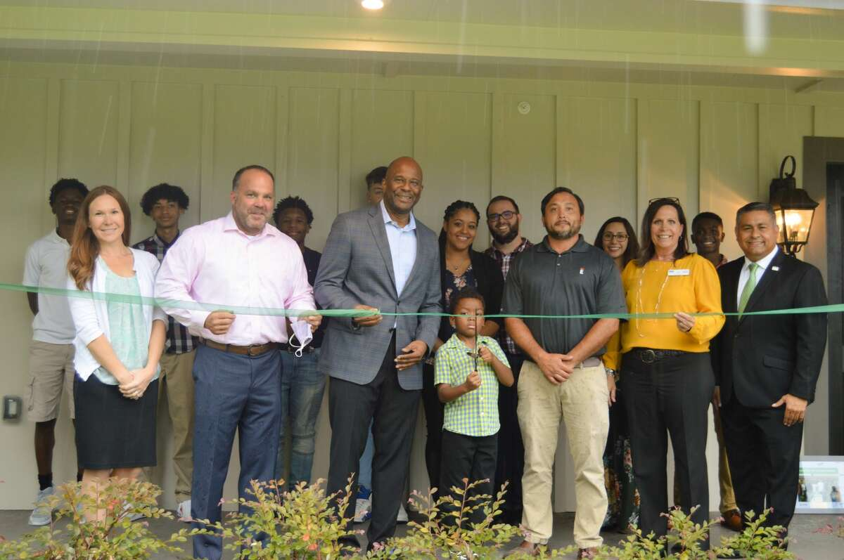 The team from HomeAid, Empire Communities and Boys and Girls Country gathered at the Woodforest Cottage to cut the ribbon symbolizing the completion of the 8,100-square-foot cottage built by Empire Communities and facilitated by HomeAid Houston.
