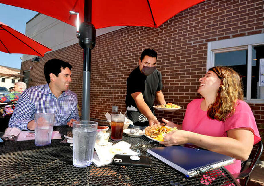 Chava's waiter Omar Jimenez, center, serves Sean Flynn of Edwardsville, left, and Jeanne Wojcieszak, also of Edwardsville at the restaurant Wednesday. Photo: Thomas Turney | For The Intelligencer