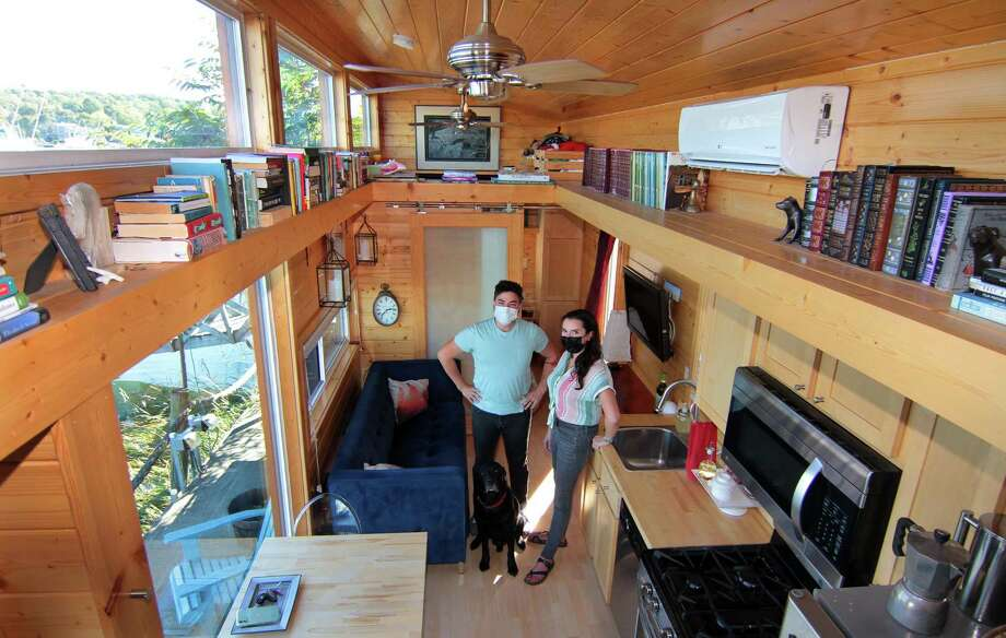 John McCarthy, his wife, Amy Garner, and their dog Winston, pose inside their tiny home along the waterfront in New Haven, Conn., on Thursday Oct. 8, 2020. Photo: Christian Abraham / Hearst Connecticut Media / Connecticut Post