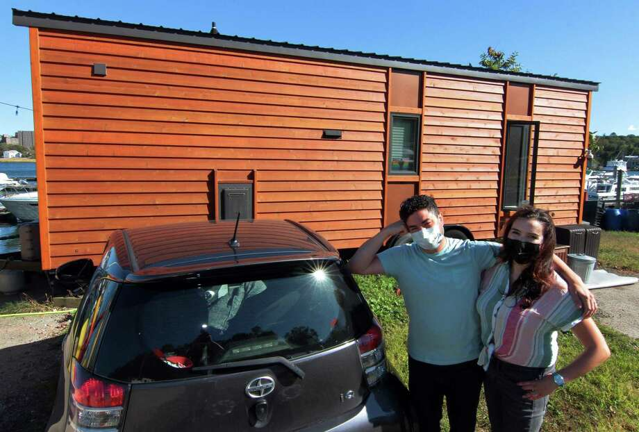 John McCarthy and his wife, Amy Garner, pose in front of their tiny home along the waterfront in New Haven, Conn., on Thursday Oct. 8, 2020. Photo: Christian Abraham / Hearst Connecticut Media / Connecticut Post