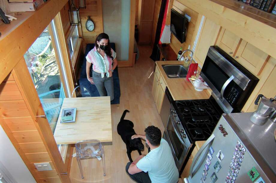 John McCarthy and his wife, Amy Garner, hang out with their dog Winston inside their tiny home along the waterfront in New Haven, Conn., on Thursday Oct. 8, 2020. Photo: Christian Abraham / Hearst Connecticut Media / Connecticut Post