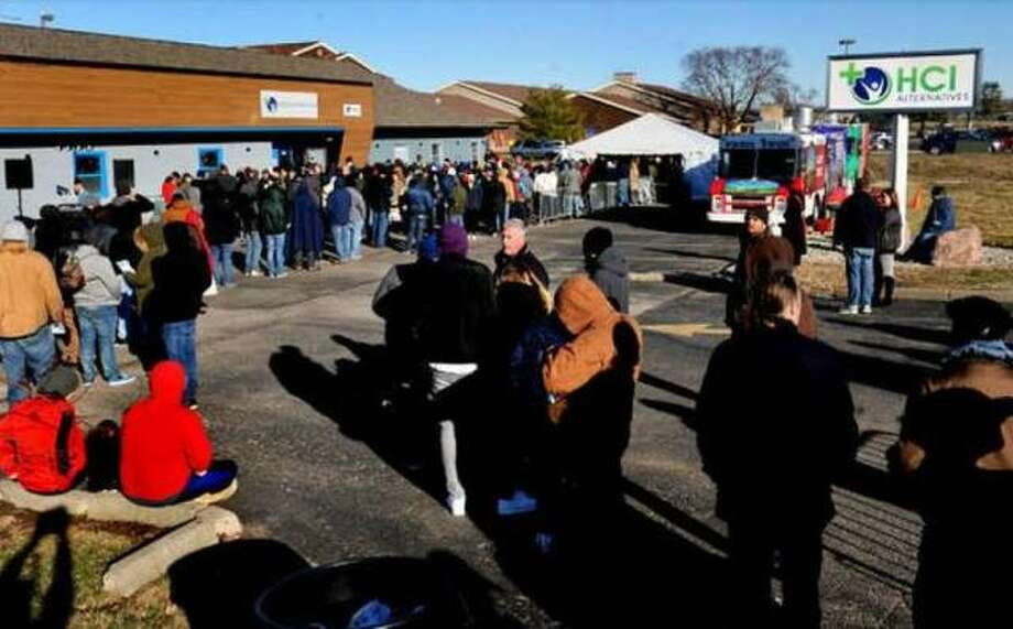 In this Jan. 1, 2020 file photo, customers lined up in front of HCI Alternatives (now Illinois Supply & Provisions) in Collinsville to purchase cannabis legally.