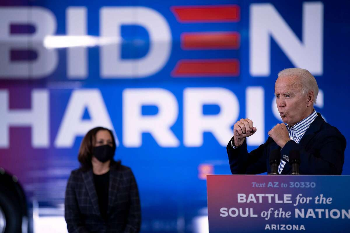 TOPSHOT - US Democratic vice presidential nominee and Senator from California, Kamala Harris (L) listens as Democratic presidential candidate former US Vice President Joe Biden speaks to supporters at the United Brotherhood of Carpenters and Joiners of America's training center, October 8, 2020, in Phoenix, Arizona. (Photo by Brendan Smialowski / AFP) (Photo by BRENDAN SMIALOWSKI/AFP via Getty Images)