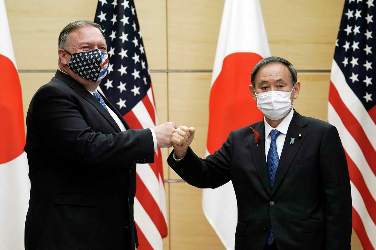 U.S. Secretary of State Mike Pompeo, left, greets Japan's Prime Minister Yoshihide Suga at the prime minister's office in Tokyo on Tuesday. One reader wonders why the U.S. didn't stick with the Trans-Pacific Partnership.