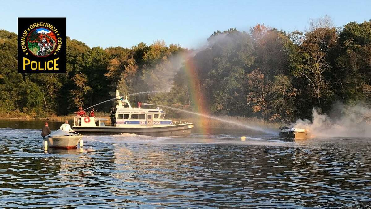 Firefighters battle a boat fire in the Cos Cob area on Friday.