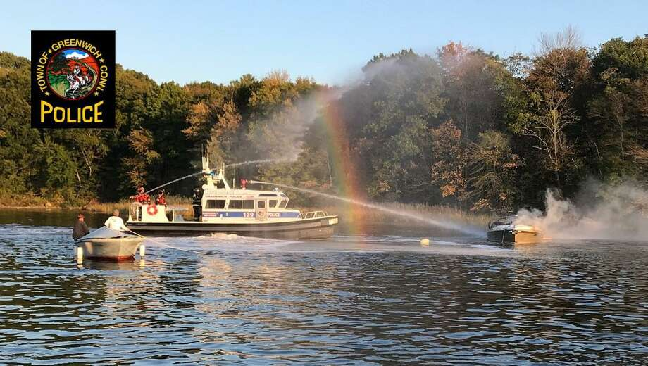 Firefighters battle a boat fire in the Cos Cob area on Friday. Photo: / Greenwich Police Department