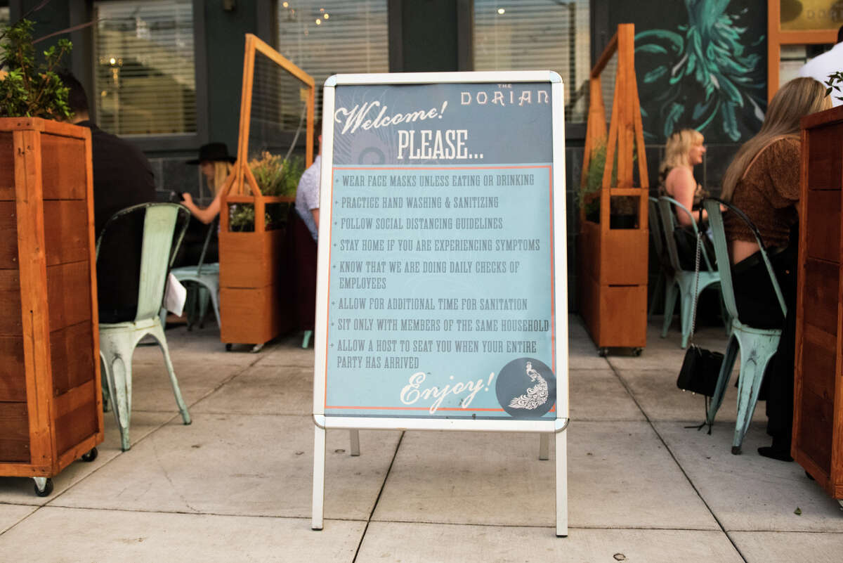 A sandwich board out front of The Dorian restaurant in the Marina displays their safety guidelines.