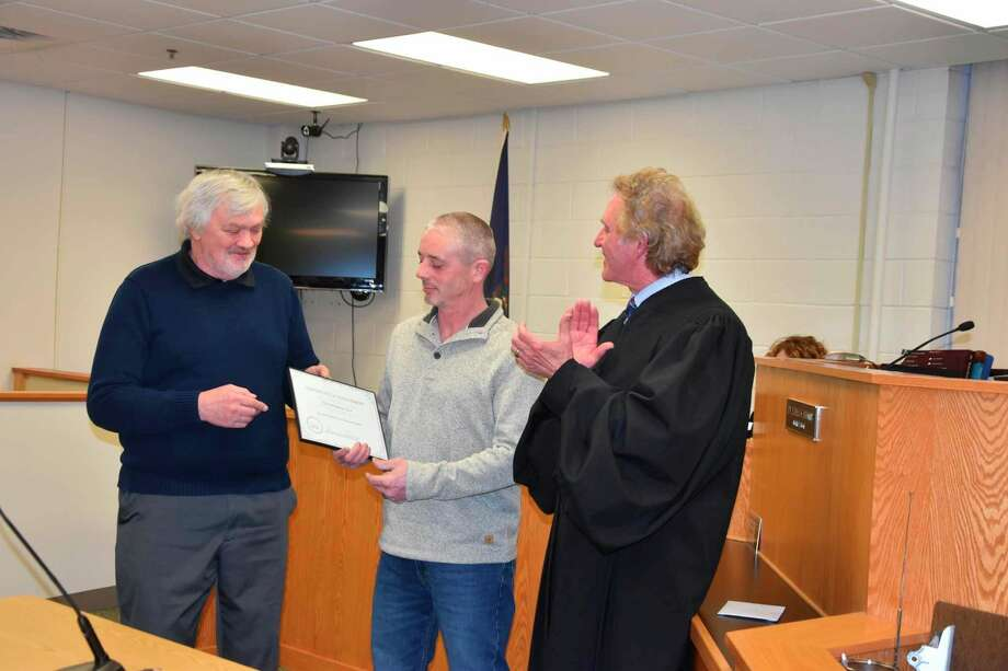 District Judge Thomas Brunner (right) and Daryl Goodman (left), sobriety court case manager, handed Chris Gee (center) his certificate of achievement and a card after telling the courtroom full of sobriety court team members, participants and supporters how much of a pleasure it had been to work with Gee in the program. Gee was the program's first graduate and he finished the program in February. (File photo)