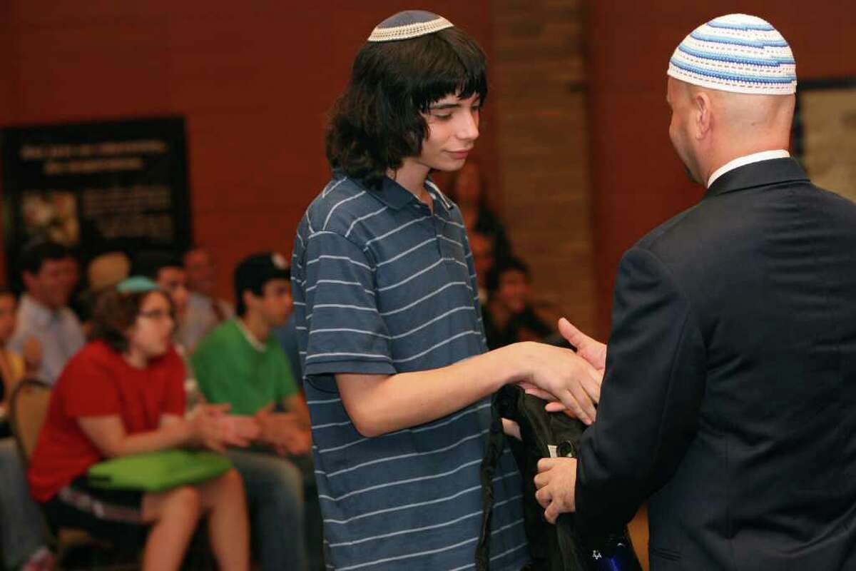 Student Zev Feller, of Stamford, receives a welcome gift at the dedication of the Jewish High School of Connecticut in Bridgeport on Monday, August 30, 2010.