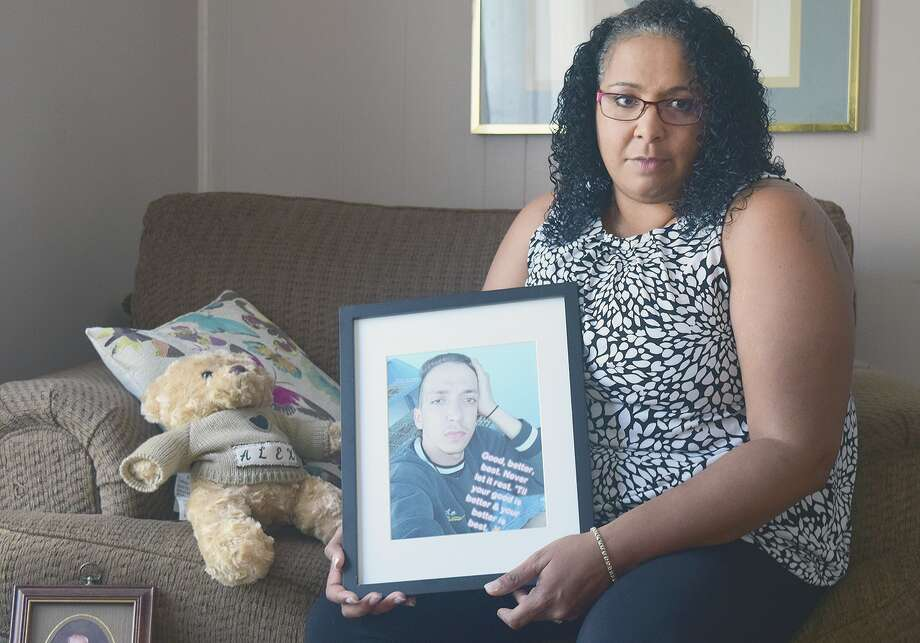 LaLonna Jackson holds a photo of her son Alex. Her year-long wait for answers about his killing took a turn when two people were arrested. She is sitting next to a teddy bear in which Alex's ashes have been stored. Photo: Marco Cartolano | Journal-Courier