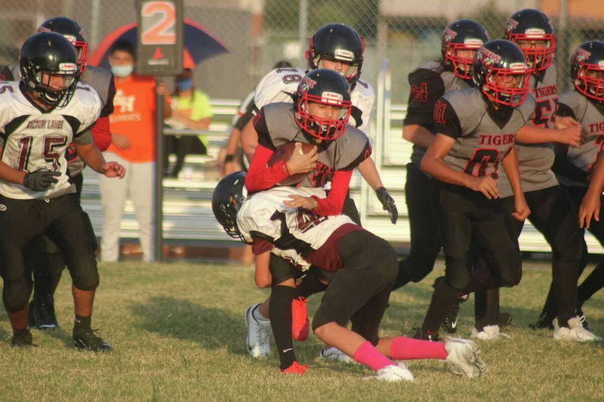 A San Jacinto Intermediate School eighth-grade B team ballcarrier get stopped at the line of scrimmage by a Victory Lakes defender. To fill gaps in their schedule, Pasadena ISD intermeidate schools have looked outside the district to schedule games.