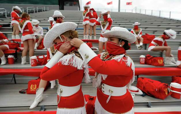 Porter dancers Lexis Large, left gets help putting up her hair from Lexi Blackwell before a District 8-5A high school football game at Randall Reed Stadium, Friday, Oct. 9, 2020, in Porter. Photo: Jason Fochtman, Staff Photographer / 2020 © Houston Chronicle