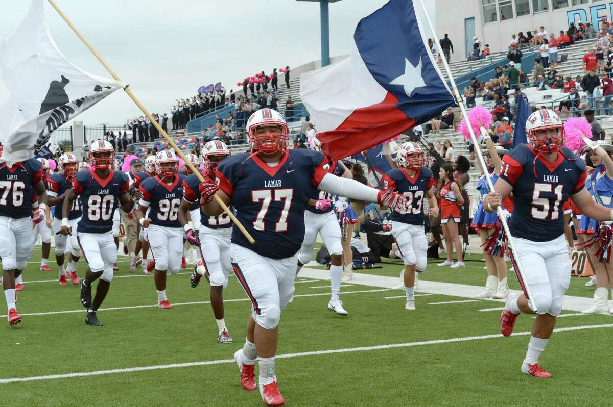 Andy Merida (77) and Will Martinez (51) lead the Lamar Texans onto the field for a high school football game with the Bellaire Cardinals on Saturday, October 20, 2018 at Delmar Stadium, Houston, TX.