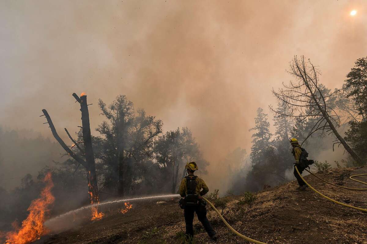 Cal Fire firefighters monitor a controlled burn to fight the Glass Fire near Calistoga. Last weekend, Cal Fire detained a crew of private firefighters for allegedly setting illegal backfires. Fire officials say the number of private firefighting crews is rising, and with it the potential for more conflicts in the fire zone.
