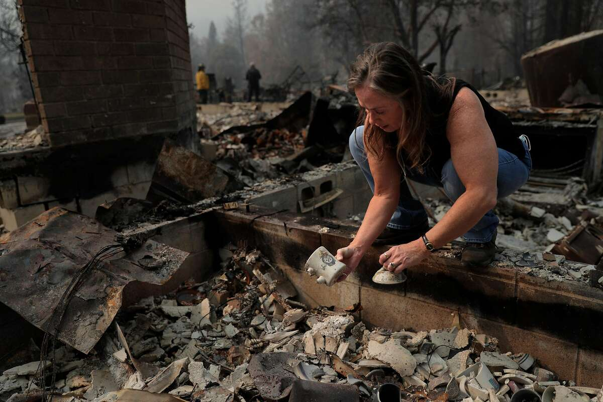Erin Hillman, a member of the Karuk Tribe, looks through the rubble of her burned home in Happy Camp (Siskiyou County).