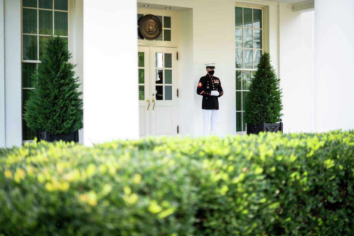 A Marine stands watch outside the West Wing, a sign that the president is in the Oval Office. President Trump is claiming to be cured after his recent bout with covid-19.