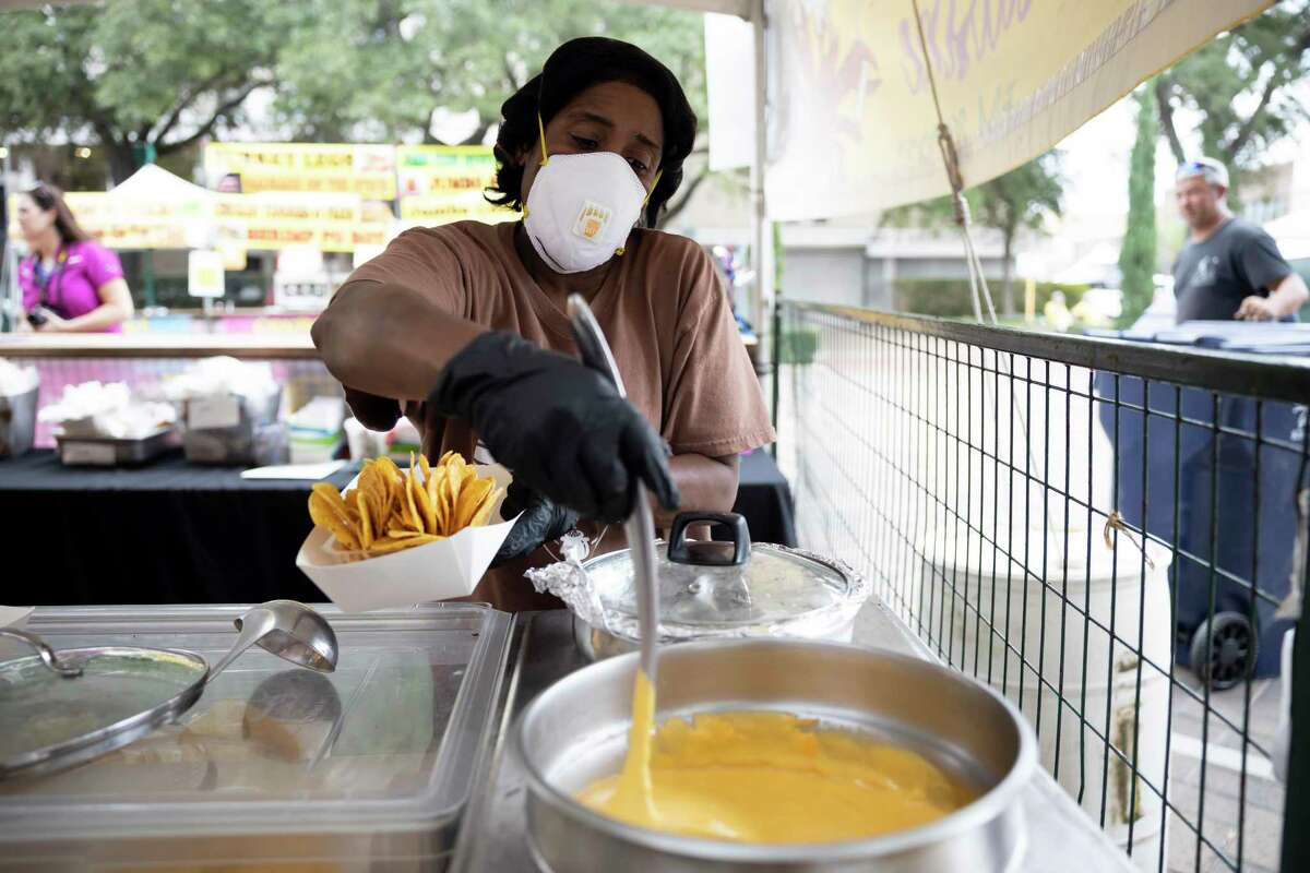 Carla Harris, owner of Mardi Gras's Cajun Cuisine, prepares a bowl of cajun nachos at the Conroe Cajun Catfish Festival on Friday. Harris is from New Orleans and travels throughout the state to offer cajun and creole style foods.