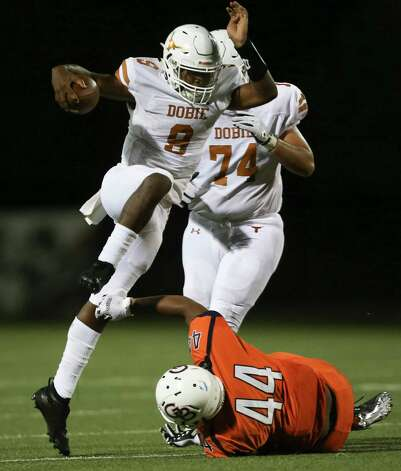 Dobie Longhorns quarterback Cameron Gray leaps over and dodges a tackle by Bush Broncos linebacker Brandon Chambers during the second quarter of the game Friday, Oct. 9, 2020, at Hall Stadium  in Missouri City. Photo: Yi-Chin Lee, Staff Photographer / © 2020 Houston Chronicle