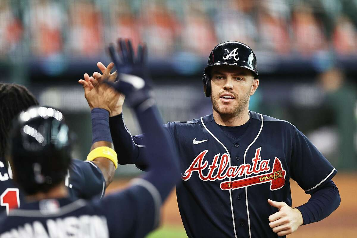 HOUSTON, TEXAS - OCTOBER 08: Freddie Freeman #5 of the Atlanta Braves celebrates scoring on a 2 RBI double by Travis d'Arnaud #16 during the third inning against the Miami Marlins in Game Three of the National League Division Series at Minute Maid Park on October 08, 2020 in Houston, Texas. (Photo by Elsa/Getty Images)
