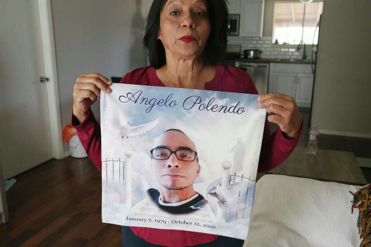 Eliza Polendo, 59, holds a tee shirt with an image of her son, Angelo Polendo, 37, at her home, Friday, Oct. 9, 2020. Her son was shot dead in October of 2016 and the case remains unsolved. Crime Stoppers has renewed the reward of up to $5,000 .